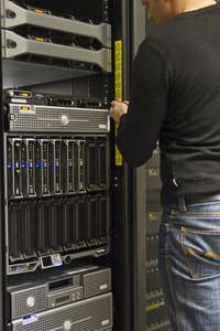 A working IT engineer / technician installing a server in a rack at the data center.