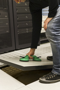 A working IT engineer / technician opens data floor for service. Shot in a datacenter.