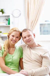 A young couple sitting on sofa and looking at camera
