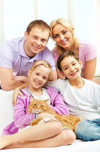 A young family of four with a cat sitting on sofa, looking at camera and smiling