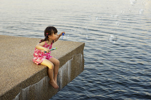 a young girl shows off her bubble making ability at the lake side