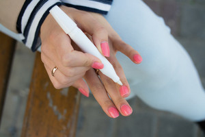 A young girl with bright pink manicure gets oil on the cuticles sitting on a bench on the street