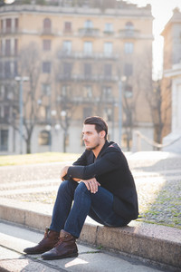 A young handsome italian boy seated on a sidewalk in the city center