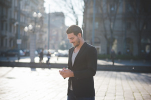 A young handsome italian boy walking through the city using a smartphone connected online- technology, social network concept