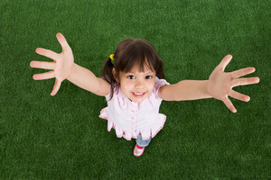 Above view of happy child standing on green grass and raising her arms to camera