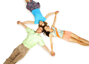 Above view of three friends holding by hands in isolation