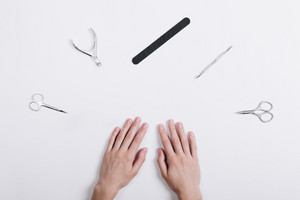 Accessories for manicure lie around a female hands on a white table top view
