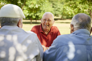 Active retired senior people, old friends and leisure, group of three elderly men having fun, laughing and talking in city park. Waist up
