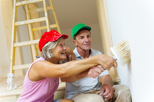 Active senior couple painting wall with brush in new house. They are having fun.