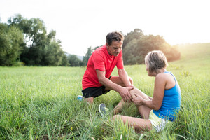 Active senior runners outside in field. Woman with injured knee. Man helping her. Green sunny summer nature.