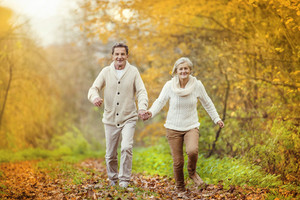 Active seniors having fun and running through the autumn forest