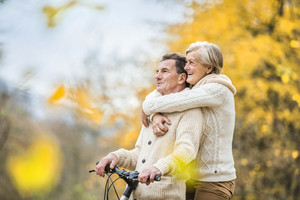 Active seniors having walk with bike in autumn nature. They having romantic time outdoor.