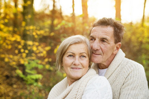 Active seniors on a walk in a park hugging