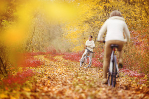 Active seniors riding bike in autumn nature. They relax outdoor.