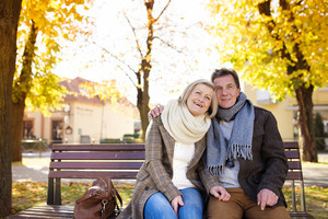 Active seniors sitting on wooden bench in autumn town