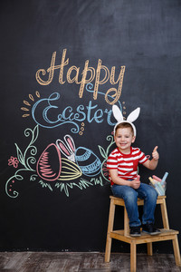 Adorable cute little boy wearing easter bunny ears and showing thumbs up gesture over chalk board with colorful text background