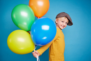 Adorable kid with balloons looking at camera