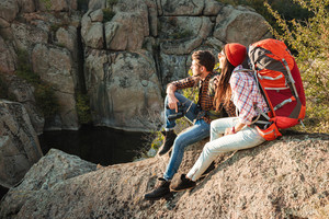 Adventure couple sitting on a rock. side view. couple looking away