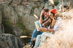 Adventure couple with map sitting on slope