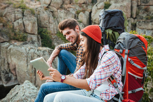 Adventure couple with tablet near the canyon. sitting at rock. side view