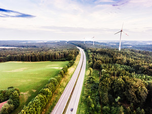 Aerial view of highway and windmills in the middle of green forest. Cloudy sky. Netherlands