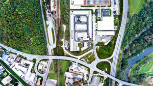 Aerial view of industrial buildings, highway and little town of Nova Bana in Slovakia surrounded by green nature.