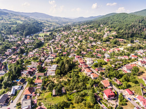 Aerial view of small town with many hills and forest surrounding it. Slovakia, Nova Bana.