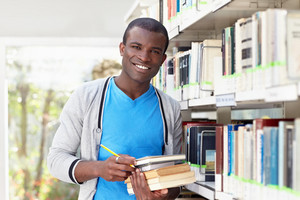 african american male college student leaning on shelf in library and looking at camera. Horizontal shape, waist up, front view