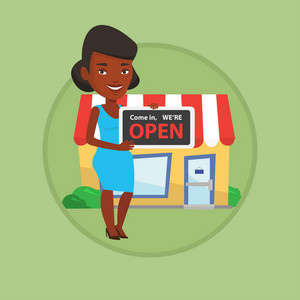 African-american shop owner holding open signboard. Shop owner standing in front of small store. Woman inviting to come in shop. Vector flat design illustration in the circle isolated on background.