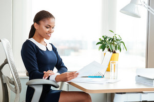 African business woman in dress sitting by the table on workplace with documents
