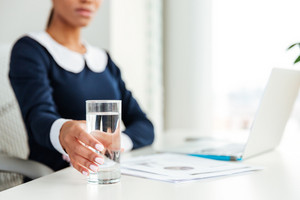 African business woman in dress sitting by the table on workplace with water. Cropped image. focus on water