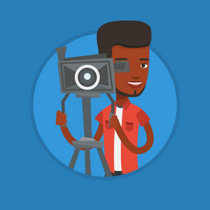 African cameraman looking through movie camera on a tripod. Cameraman with professional video camera. Cameraman taking a video. Vector flat design illustration in the circle isolated on background.
