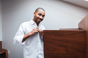 African man dresses in hotel room and looking at camera