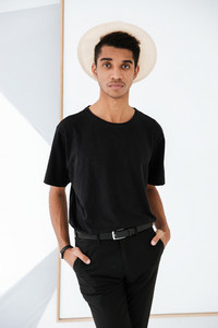 African man in black clothing and hat posing in office with hands in pocket and looking at camera