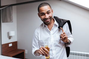 African man in shirt holding beer in hand and looking at camera in hotel room