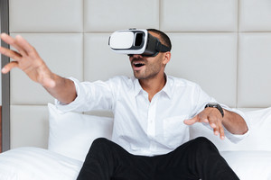 African man in shirt using virtual reality device sitting on bed in hotel