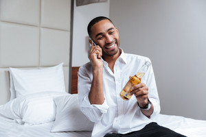 African man in shirt with beer in hand talking at phone on bed in hotel room