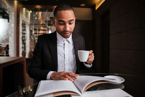 African man in suit sitting with journal and coffee in hotel