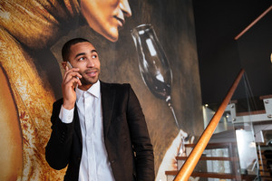 African man in suit talking at phone and standing on stairs