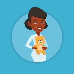 African pediatrician in medical gown. Pediatrician doctor holding a teddy bear. Pediatrician doctor standing with a teddy bear. Vector flat design illustration in the circle isolated on background.