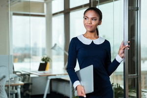Afro Business woman in dress standing with laptop in hand in office