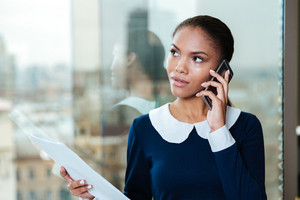 Afro Business woman in dress talking on phone and standing near the window in office