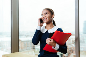 Afro Business woman in dress talking on phone with folder in hand and standing near the window