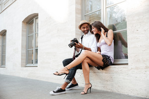 Afro photographer with young model. sitting