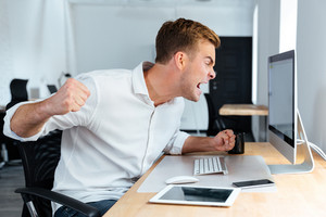 Aggressive furious young businessman shouting and working with computer in office