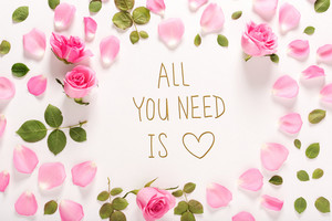 All You Need Is Love message with roses and leaves top view flat lay