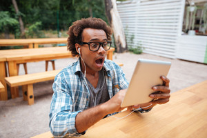 Amazed african young man in glasses with tablet sittign and shouting outdoors