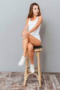 Amazed brunette woman sitting on the chair and looking away over gray background