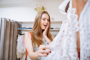 Amazed happy young woman choosing dress in clothing shop