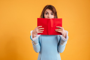 Amazed pretty young woman covered her face with red book over yellow background